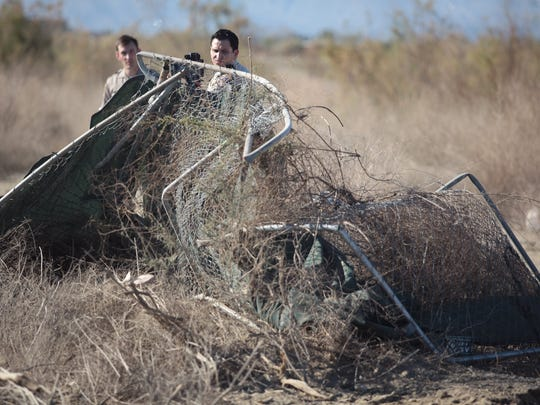 California Highway Patrol officers C. Orehek, left, and G. Johnson on Thursday examine a fence damaged when when a driver traveling west on 66th Ave in Thermal lost control of a car near Martinez Street and crashed through it.