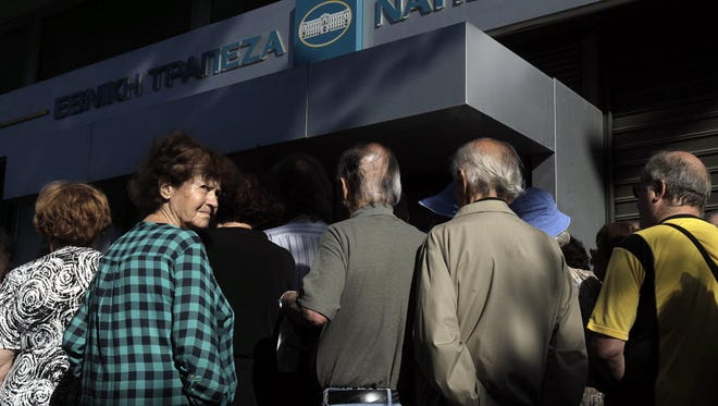 Pensioners, who do not own an ATM card, wait to get part of their pensions in front of a branch of National Bank of Greece in Athens, Greece, July 2,  2015.