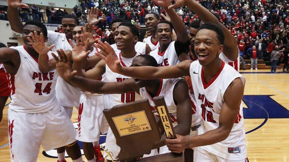 Pike's Justin Thomas (right), the team's high-scorer with 21 points, celebrates with his teammates after the school won its fifth consecutive sectional by beating the Class 4A No. 1 Southport Cardinals 49-48 in the Perry Meridian boys basketball sectional final on Saturday, March 7, 2015.