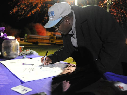 Wayne Bell writes an encouraging message on a pillowcase at Eastern Shore Coalition Against Domestic Violence's table at the Northampton High School football game on Friday, Oct. 30, 2015. The pillowcases are presented to women, men and children affected by domestic and sexual violence who enter the coalition's 24/7 emergency shelter.