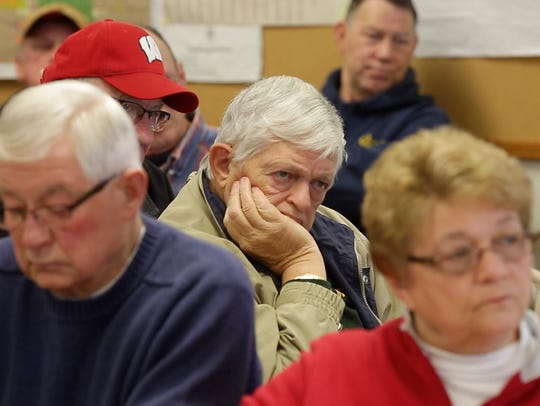 People listen to information on proposed cuts to the