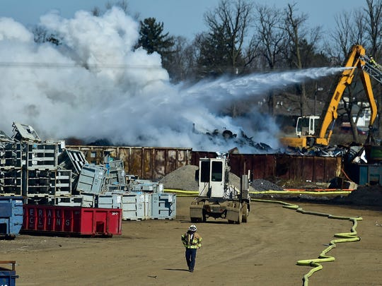 Fire hoses snake across the ground as crews battle a Thursday morning fire at Sims Brothers Recycling.