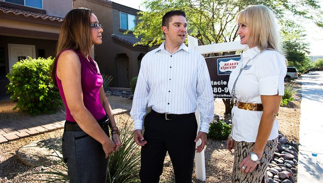 Maria and Chris Ratka (left) speak with their real estate agent, Stacie Neumann, in front of their house in north Phoenix.