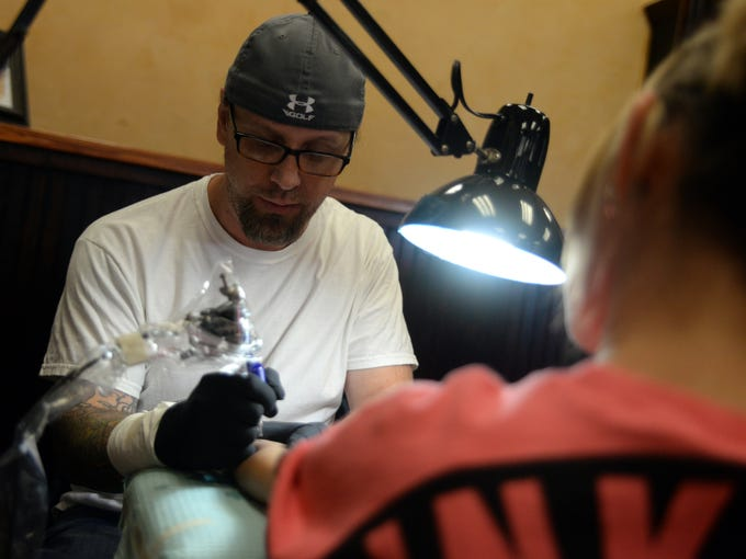 Tattoo artist Eric Hooven begins inking a tattoo on