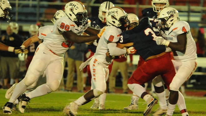 Blackman's Ben Kalu (90), Jamis Carson (8) and Jordan Brown (4) combine to tackle Cookeville's David Gist (3) in the second quarter of Friday's game at Cookeville.
