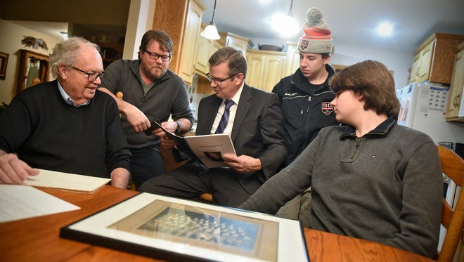Benson family members, from left, Bob, Patrick, Mark, Thomas and Tyler, look over materials detailing family history during an interview Wednesday, Dec. 13, in St. Cloud. George Benson, Bob's father, was a member of the first Technical High School graduating class in 1917. His great-grandsons Thomas and Tyler will be in the last graduating class from the current building.