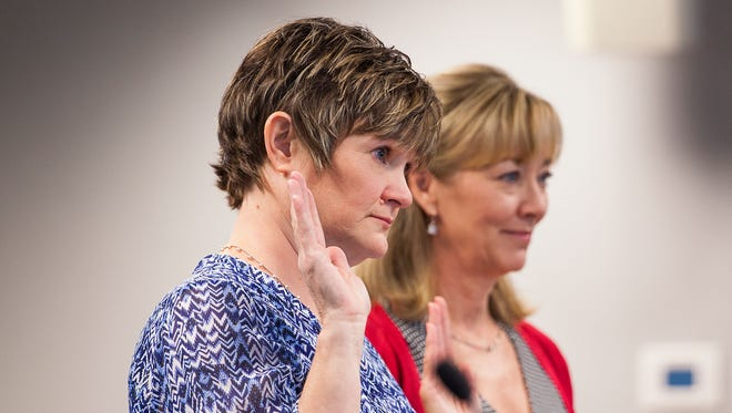 Julie Nowak, left, is sworn in before the Virginia Board of Nursing during her license hearing in Richmond. Nowak is no stranger to drug monitoring. When a previous employer reported her for substance abuse in 1996 — the same year she got her RN license — she enrolled in a peer assistance program. After completing it, her license was cleared.