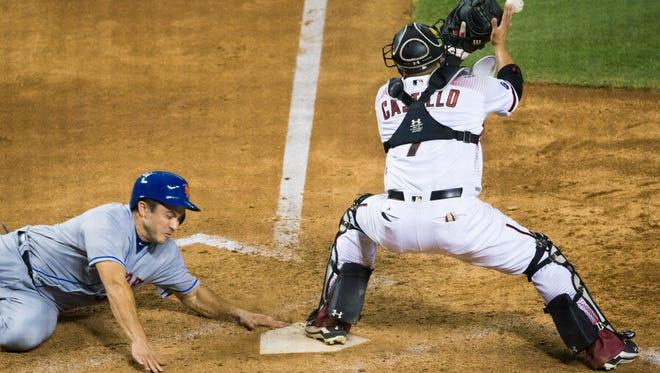 New York Mets base runner Travis d'Arnaud scores ahead of the tag by Arizona Diamondbacks catcher Welington Castillo  at Chase Field in Phoenix August 15, 2016.