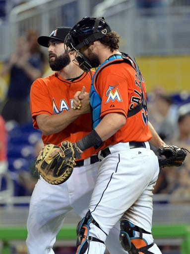 Aug 16, 2014: Miami Marlins relief pitcher Chris Hatcher (left) shake hands with catcher Jarrod Saltalamacchia (right) after defeating the Arizona Diamondbacks 10-3 at Marlins Ballpark.