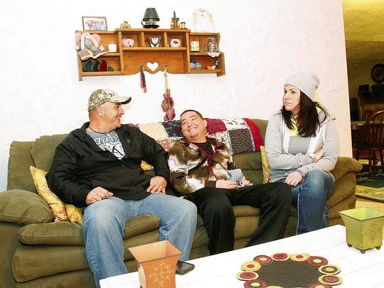 David Montoya, left, Justin Solomon and Jenn Solomon talk about a recent hunting experience Thursday at Derek Martin's home in Farmington.