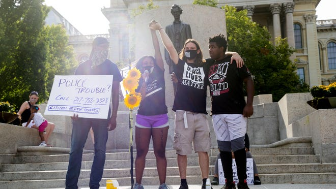 Flanked by Leroy Newbon, left, John Keating and William Crawford, Shaunna Kirk raises her arm in solidarity as she talks about the need for action during the Justice for Jacob Blake rally at the Capitol on Saturday. The rally was organized by Progressive Voices of Central Illinois, a coalition of grassroots and community activism organizations, the Springfield-based group In Black Ink and Kirk.