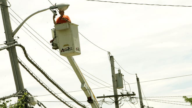 A city worker replaces a street light cell in Peekskill.