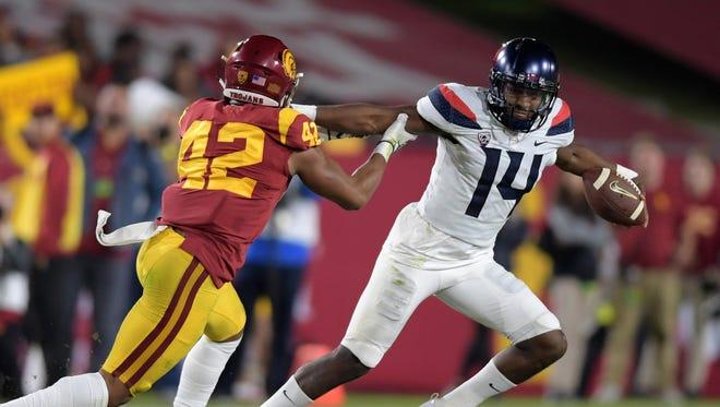 Arizona Wildcats quarterback Khalil Tate (14) is pressured by Southern California Trojans linebacker Uchenna Nwosu (42) during an NCAA football game at Los Angeles Memorial Coliseum.