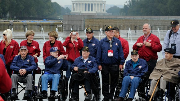 Central California veterans and escorts pose for photographs during a visit to the World War II Memorial in Washington as part of the Honor Flight program in 2013.