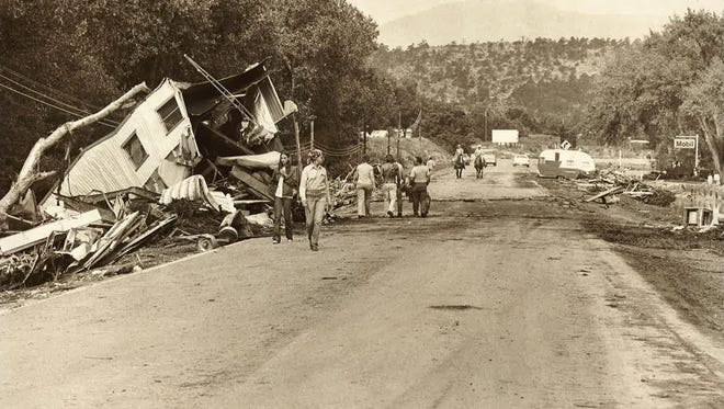 Residents and rescuers walk among the destroyed homes, businesses and roads in areas near the Big Thompson Canyon after the flood on July 31, 1976. The disaster caused more than $35 million in damages (1977 figures) to 418 homes and businesses as well as 438 vehicles.