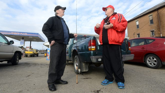Roger Ross and Steve Handa, left, chat in the parking lot of John's Place in Corning after Ross returned Handa's fishing pole to him. Ross rescued Handa after Handa fell out of his fishing boat at Burr Oak State Park last month, and later returned to find Handa's lost fishing pole.