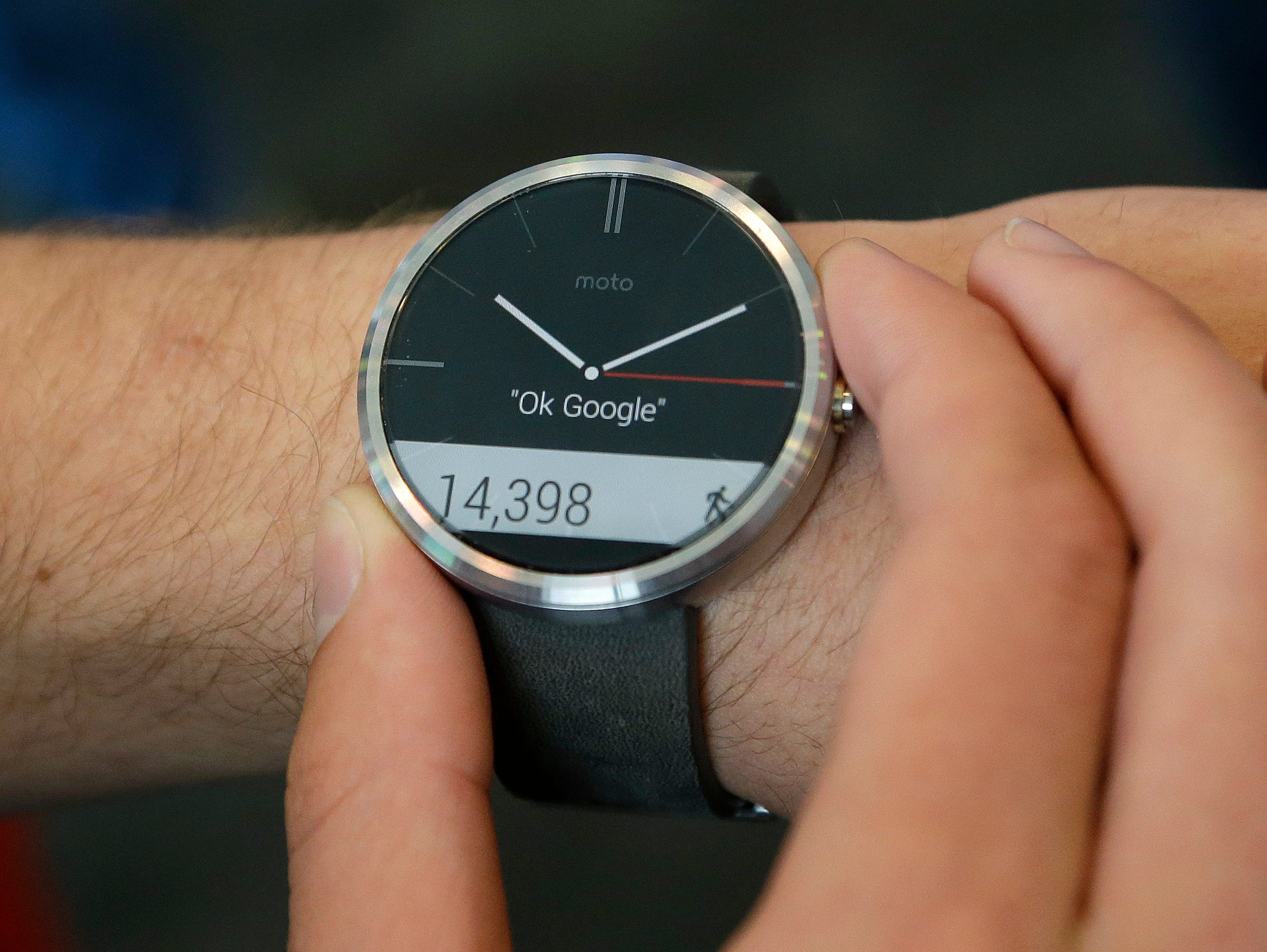 A man wears a Moto 360 by Motorola, an Android Wear smartwatch, on the demo floor at Google I/O 2014 in San Francisco on June 25, 2014.