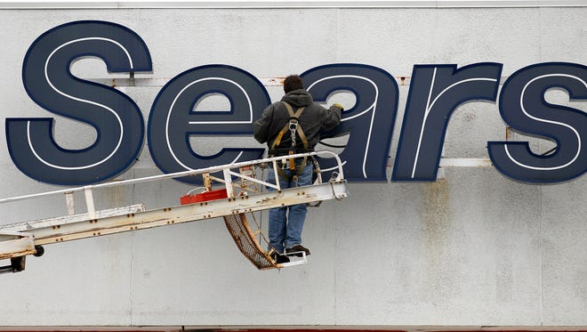 FILE - In this Feb. 13, 2012, file photo, a worker repairs the Sears sign outside the Sears Grand store in Solon, Ohio. Sears Holdings Corp. reports quarterly financial results before the market opens, Monday, June 8, 2015. (AP Photo/Amy Sancetta. File) ORG XMIT: NYBZ120
