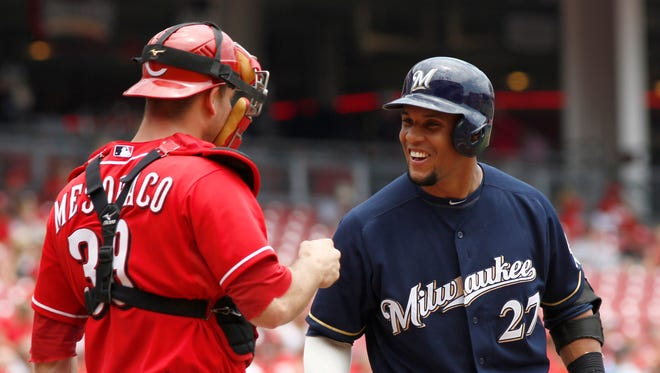 Milwaukee Brewers center fielder Carlos Gomez (27) talks with Cincinnati Reds catcher Devin Mesoraco (39) at home plate during the second inning at Great American Ball Park.