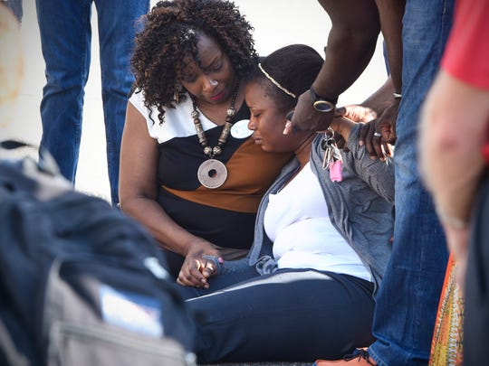 A woman is comforted after falling to the ground Thursday during a vigil for Keletigui Keita at Kilimandjaro Market in St. Cloud.