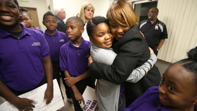 Dunbar Elementary fourth-grade student Camya Everett (center), gets a hug from Dunbar principal Dr. Anniece Gentry after SCS Superintendent Dorsey Hopson withdrew his proposal to close the school.