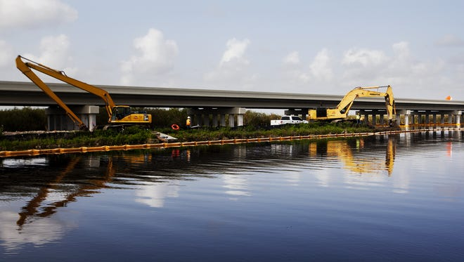 Work progresses on a Tamiami Trail bridge that was recently built over the southeastern Everglades near Shark Valley. Water is being released in this area to relieve flooding across the region.