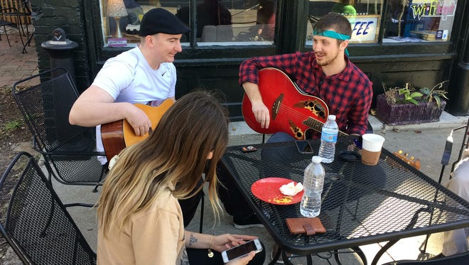 Jared Beamer (right) performing outside Penny Lane Coffeehouse Tuesday for a concert paying tribute to his friend and  mother who recently died.
