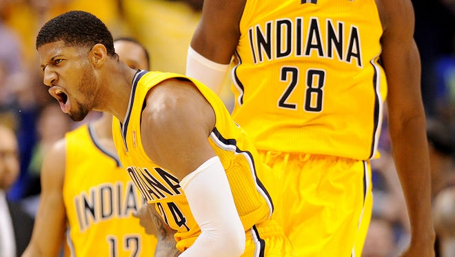Indiana Pacers forward Paul George and center Ian Mahinmi celebrate a dunk inside Bankers Life Fieldhouse, March 26, 2014, in Indianapolis.