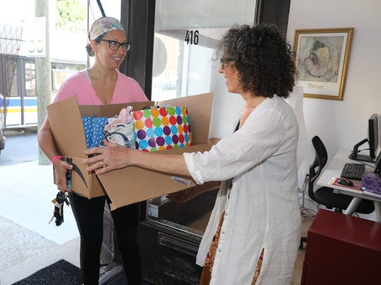 """Pam Koner, right, the executive director of Family-to-Family in Hastings-on-Hudson, accepts a box of """"birthday parties in a bag"""" items from Lauren Franklin, June 29, 2018. The center has been collecting items for unaccompanied immigrant children being held at Children's Village in Dobbs Ferry."""