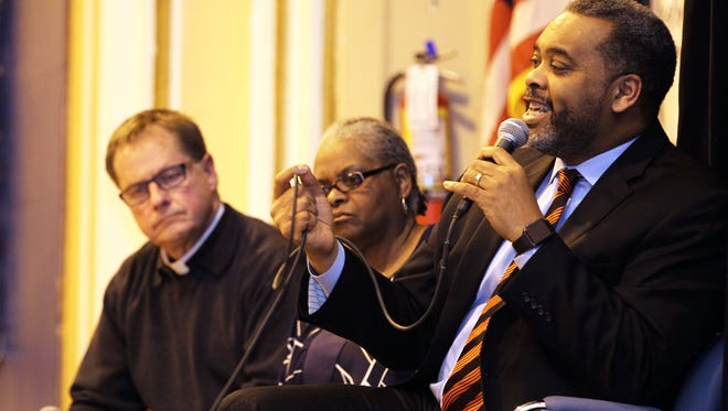 The Rev. Walter Lanier (right) of Progressive Baptist Church comments at the forum. Joining him on stage are the Rev. Tim Kitzke (left), the vicar general for urban ministry for the Milwaukee Archdiocese, and the Rev. Marilyn Miller, president of Milwaukee Inner City Congregations Allied for Hope.