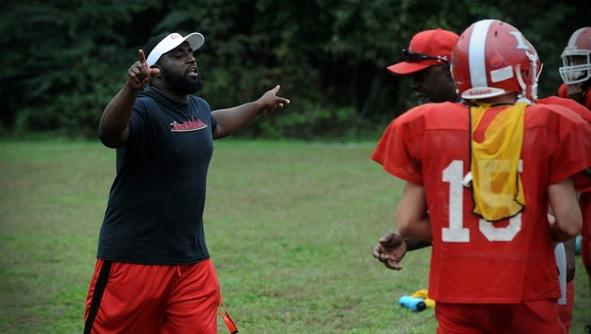 Laurel head coach Eston Ennis instructs players during a Bulldogs' practice on Tuesday, Sept. 27, 2016 in Laurel.