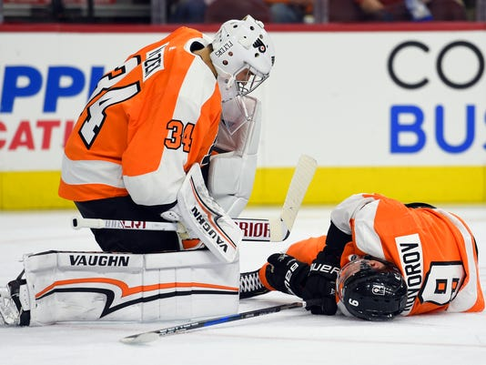 Philadelphia Flyers goalie Petr Mrazek, left, looks over injured teammate Ivan Provorov after Provorov blocked a shot during the first period of an NHL hockey game against the Carolina Hurricanes, Thursday, March 1, 2018, in Philadelphia. (AP Photo/Derik Hamilton)