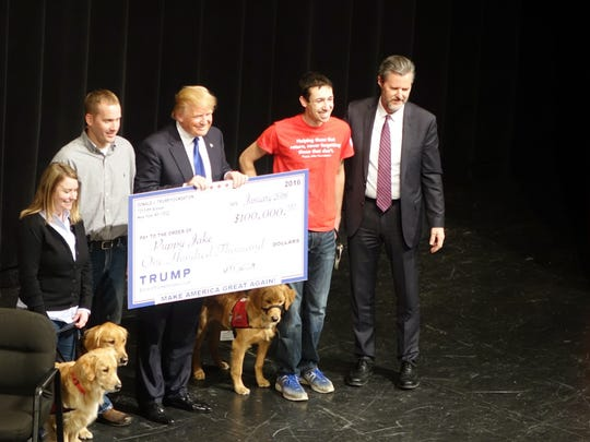 Donald Trump beams as he hands over a check for $100,000 to the Puppy Jake foundation. Trump raised the money earlier in the week after skipping the Republican debate and hosting a fundraiser to support veterans and veteran service organizations.