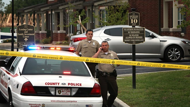 Police investigate a fatal shooting Sept. 18, 2014, in Jennings, Mo.