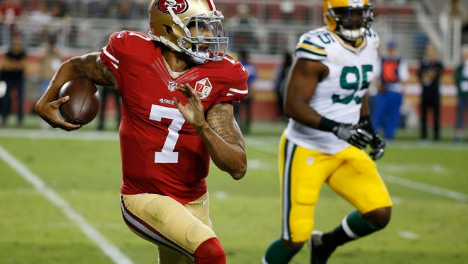 San Francisco 49ers quarterback Colin Kaepernick, left, runs with the ball as Green Bay Packers defensive end Datone Jones pursues during the first half of an NFL preseason football game Friday.
