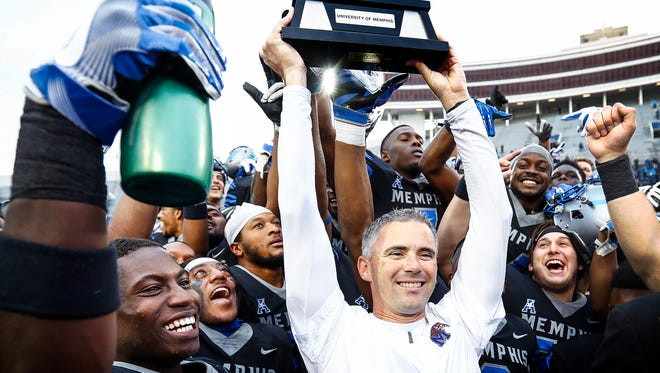 Memphis head coach Mike Norvell (middle) surrounded by his players holds ups the American Athletic Conference West Division Championship trophy after defeating SMU 66-45 in Memphis, Tenn., Saturday, November 18, 2017.