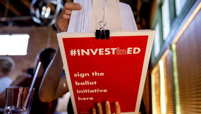 Amber Yudell, of Phoenix, looks at papers on June 20, 2018, at Mother Bunch Brewery in Phoenix. Arizona Educators United members are collecting signatures in favor of the Invest in Education Act that would fund education by raising income taxes on Arizona's highest earners.