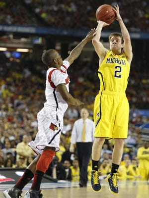Michigan's Spike Albrecht hits a three point shot over a Louisville defender in the first half during the 2013 NCAA championship game between Michigan and Louisville at the Georgia Dome in Atlanta on Monday, April 8, 2013.