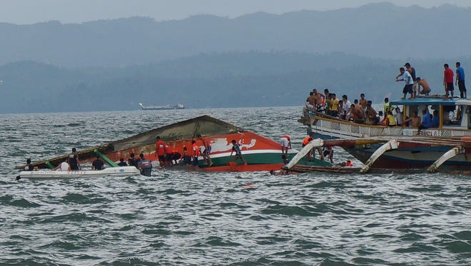 Rescuers help passengers from a capsized ferry boat, center, in Ormoc city on Leyte Island, Philippines, on Thursday, July 2, 2015.