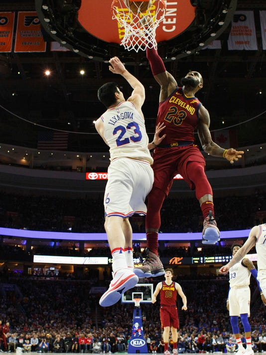 Cleveland Cavaliers' LeBron James, right, dunks the ball against Philadelphia 76ers' Ersan Ilyasova, left, of Turkey, during the second half of an NBA basketball game, Friday, April 6, 2018, in Philadelphia. (AP Photo/Chris Szagola)