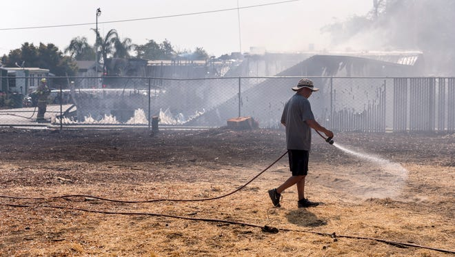 Eddie Dominguez sprays his backyard as the Visalia Fire Department responds to a mobile home fire south of Mooney Grove Park on Sunday, July 29, 2018.