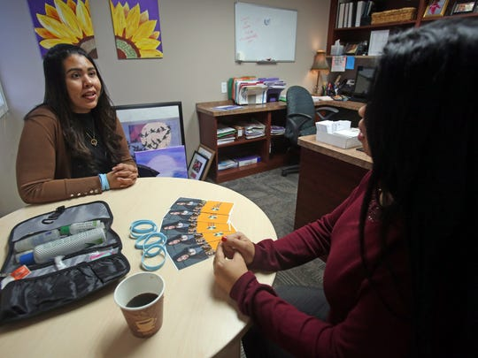 Dariela Vasquez, left, the coordinator of anti-human trafficking services talks with co-worker at the Center for Safety and Change in New City Jan. 23, 2018.