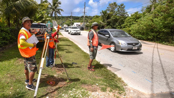 Department of Land Management's only survey crew, from left, Albert Pascua, Dave Delgado and Peter Esteban, prepare to record measurements along Macheche Road in Dededo on Tuesday, May 16, 2017. Replacement of sewer lines along a section of the roadway is schedule to begin on May 17, according to Heidi Ballendorf, Guam Waterworks communications manager.