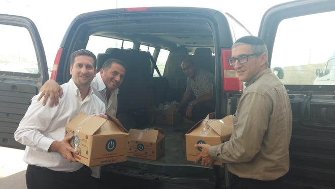 David Nekrutman, executive director of the Center for Jewish Christian Understanding and Cooperation in Jerusulem, Pastor Hani Khayo, Pastor Ziyad Bannoura and Rabbi Pesach Wolicki pack boxes to deliver to members of the First Baptist Church of Bethlehem last week. The group is delivering food in a program modeled after the Faith Temple food giveaway in Sioux Falls.