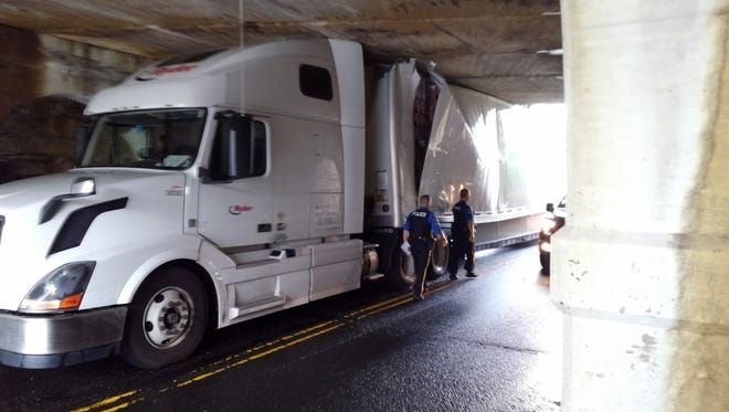 A tractor-trailer became wedged under an overpass in Jamesburg on Monday.