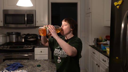 Laura Kaufman drinks apple juice in the kitchen on