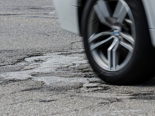 A tire rolls over a rough section of Warren Road that local officials hoped would be repaired this year.