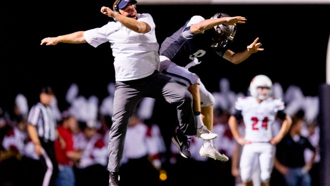 Anderson County Head Coach Davey Gillum celebrates with quarterback Stanton Martin after he ran a 34-yard scarmble to finish the first half of the game with ascore of 42-10 during a game between Anderson County and Heritage at Anderson County High School in city}, Tennessee on Friday, September 22, 2017.