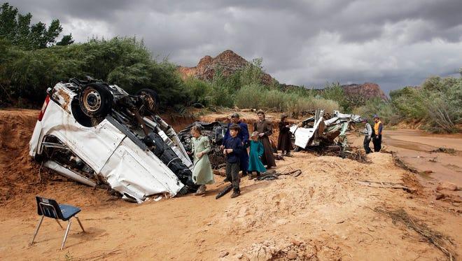 People walk pass damaged vehicles  swept away during a flash flood Tuesday, Sept. 15, 2015, in Hildale, Utah. The floodwater swept away multiple vehicles in the Utah-Arizona border town, killing several people.