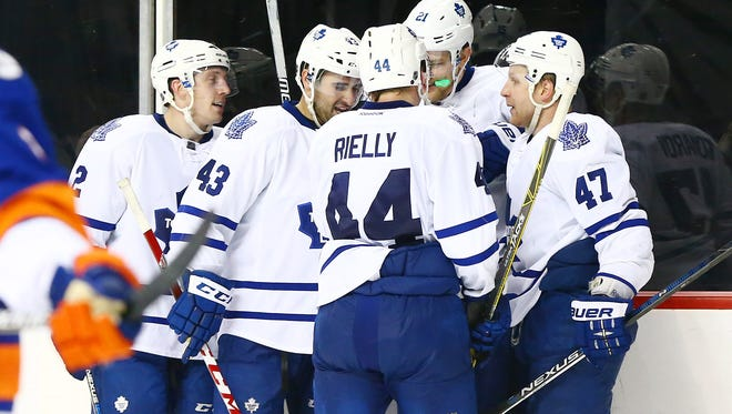 Toronto Maple Leafs left wing James van Riemsdyk (21) is congratulated after scoring an empty net goal late in the third period against the New York Islanders at Barclays Center.